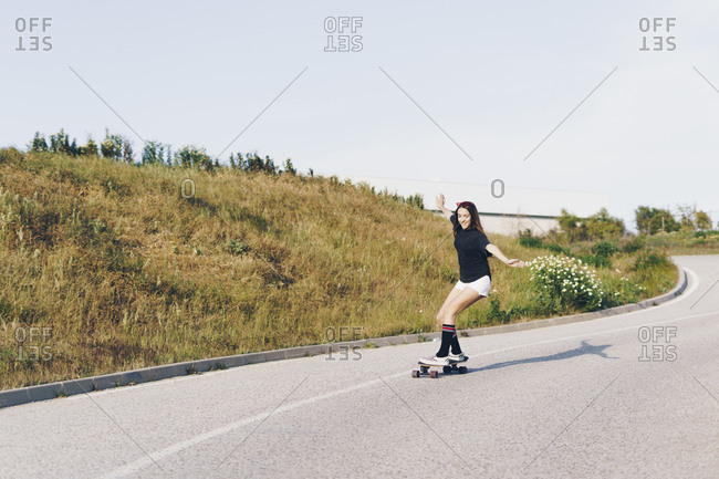 Spain- teenage girl riding skateboard down a road