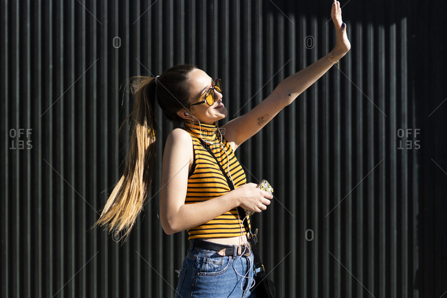 Happy teenage girl with earphones and smartphone enjoying the sunshine