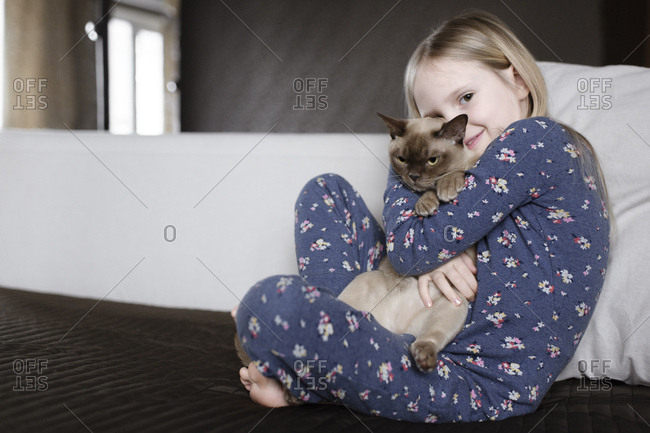 Portrait of smiling little girl wearing pajama with floral design holding cat