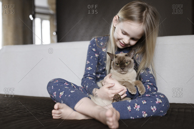 Smiling little girl wearing pajama with floral design at home holding cat
