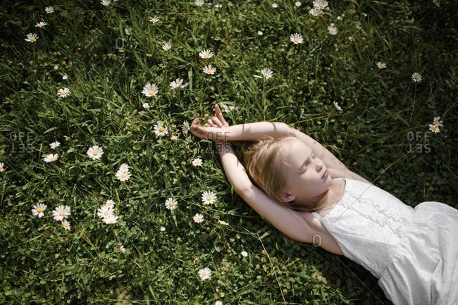 Little girl lying in flower field