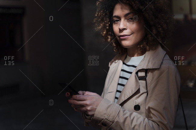 Portrait of confident woman in an alley holding cell phone