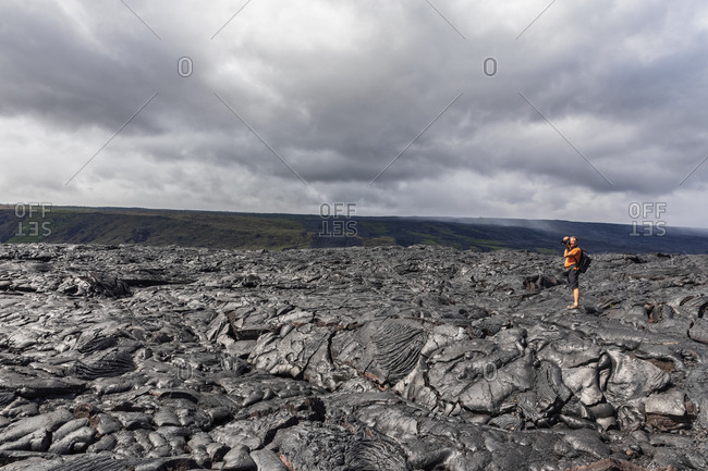 USA- Hawaii- Big Island- Volcanoes National Park- photographer on lava field along Chain of Craters Road