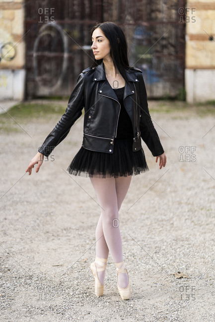 Italy- Verona- Ballerina dancing in the city wearing leather jacket and tutu