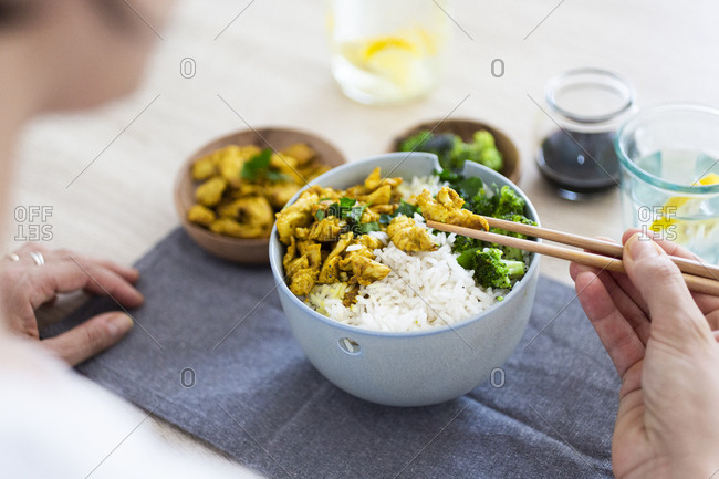 Curry chicken- broccoli and rice- woman with chopsticks