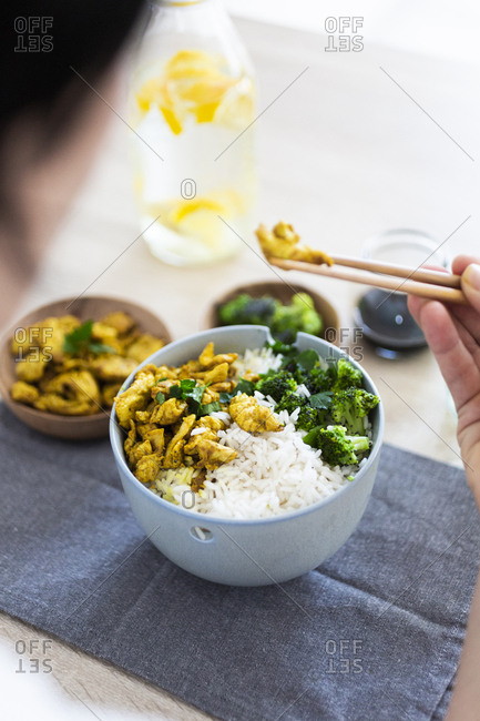 Curry chicken- broccoli and rice- woman eating with chopsticks