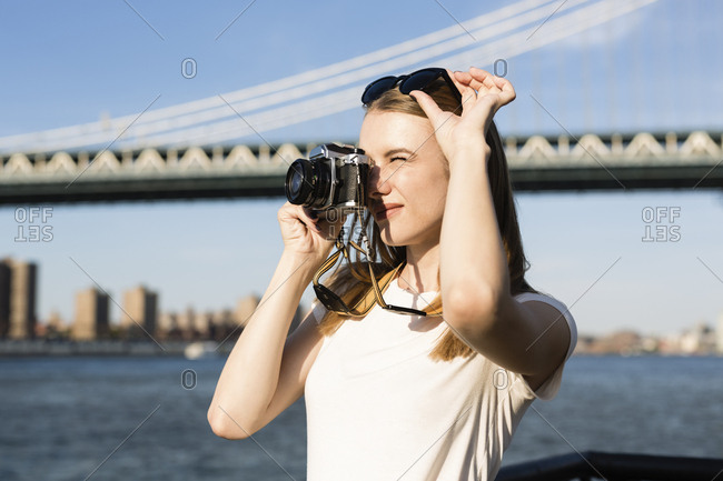 Young woman exploring New York City- taking pictures at Brooklyn Bridge