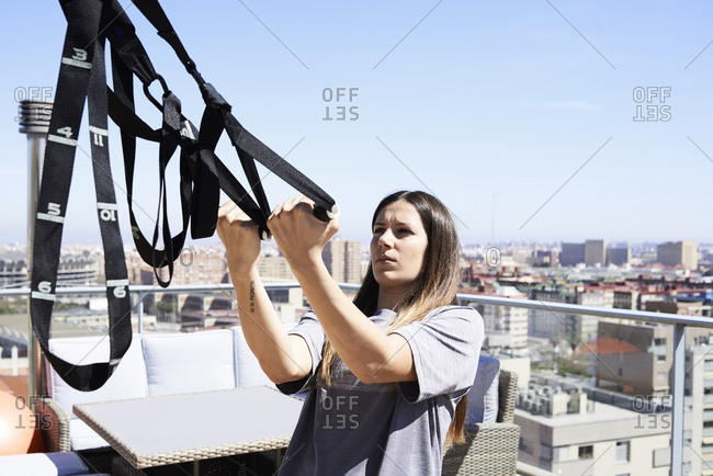 Sporty young woman doing suspension training on roof terrace