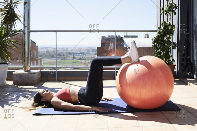 Sporty young woman exercising with fitness ball on roof terrace