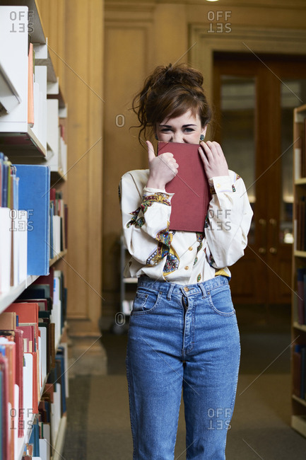 Female student reading book in a public library