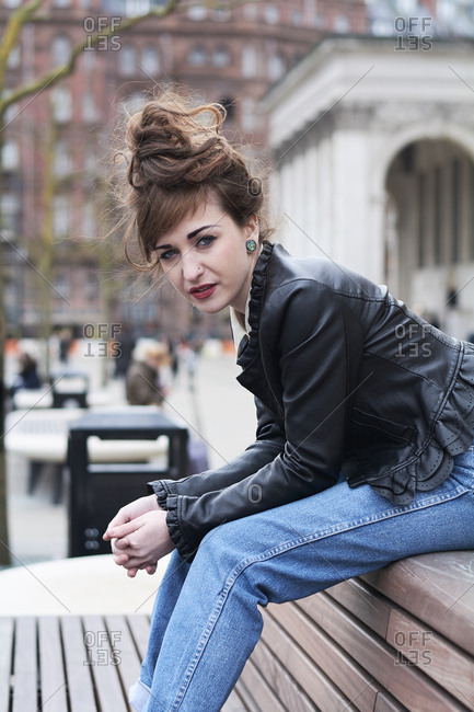 Young woman sitting on a bench in Manchester