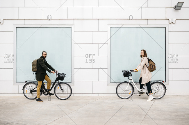 Portrait of man and woman with e-bikes standing at a building