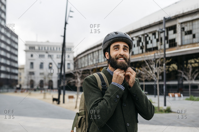 Portrait of smiling man putting on bicycle helmet in the city