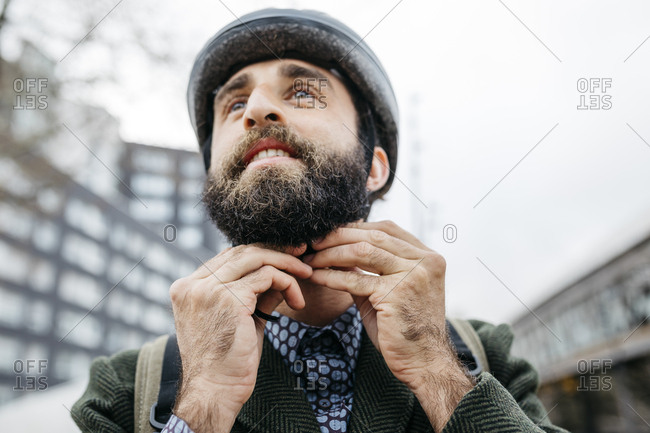 Portrait of man putting on bicycle helmet in the city