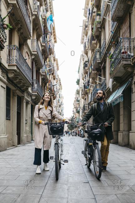 Couple pushing e-bikes exploring the city