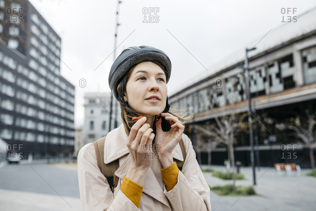 Portrait of woman putting on bicycle helmet in the city