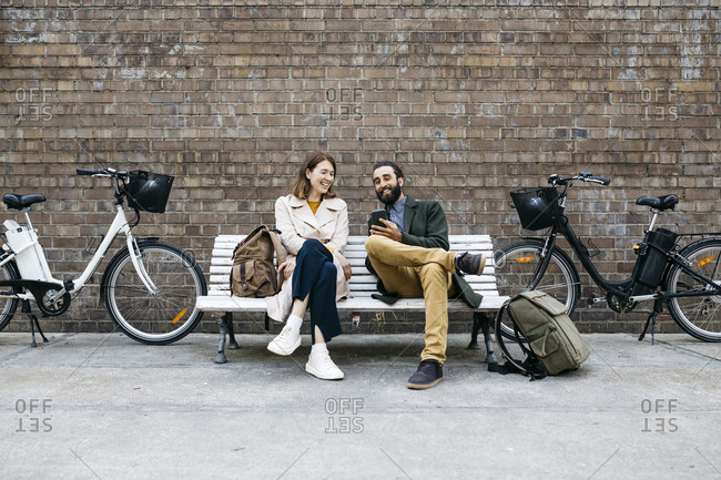 Happy couple sitting on a bench next to e-bikes sharing cell phone