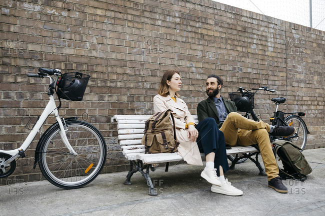 Couple sitting on a bench next to e-bikes talking