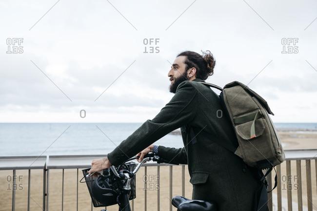 Man with e-bike having a break on beach promenade