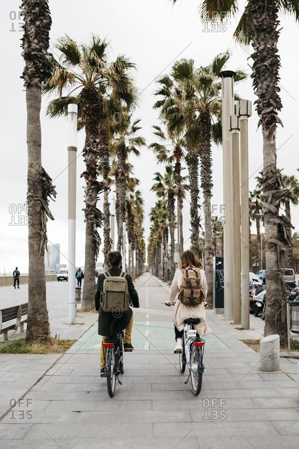 Rear view of couple riding e-bikes on a promenade
