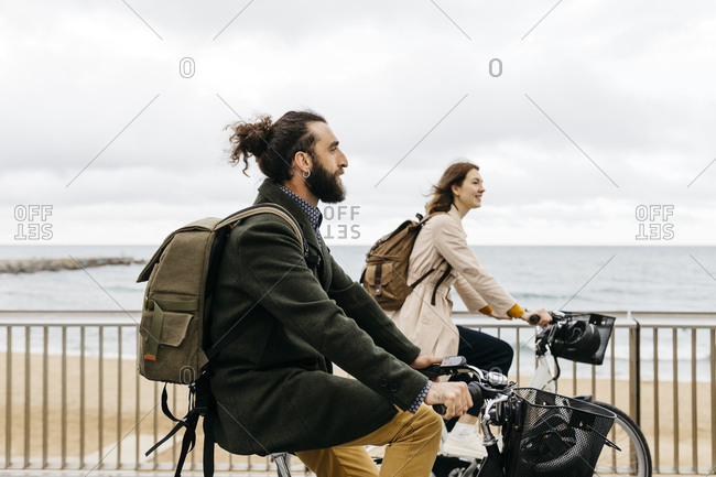 Couple riding e-bikes on beach promenade