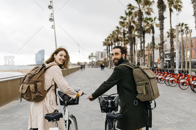 Smiling couple with e-bikes on beach promenade