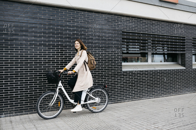 Woman riding e-bike along a brick wall in the city