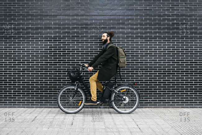 Man riding e-bike along a brick wall