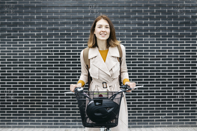 Portrait of smiling woman with e-bike at a brick wall