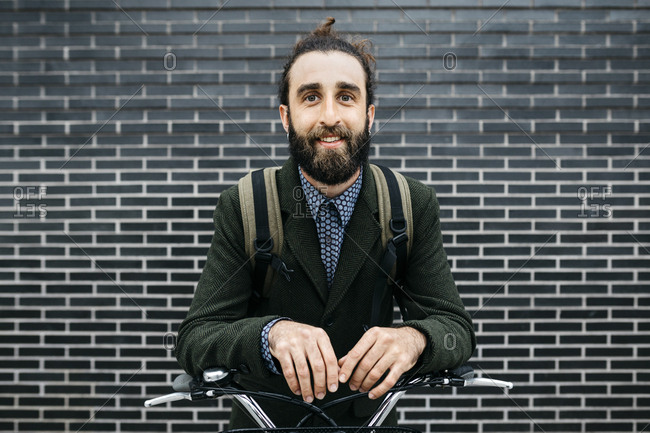 Portrait of smiling man with e-bike at a brick wall
