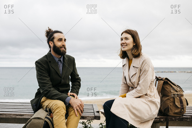 Smiling couple sitting on a bench at beach promenade talking