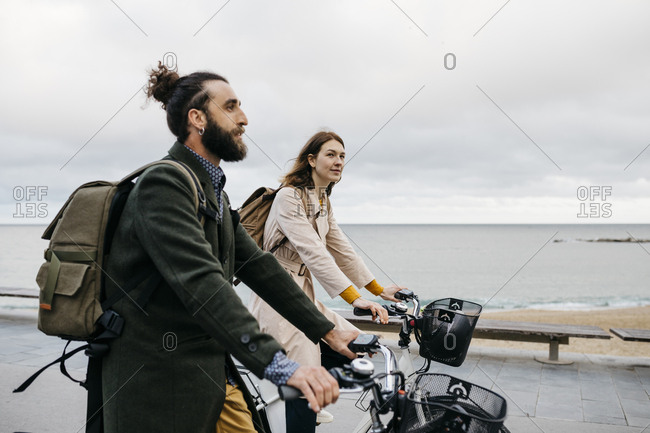 Couple riding e-bikes on beach promenade