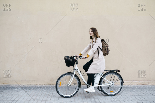Woman riding e-bike along a wall
