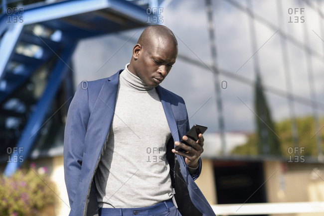 Businessman wearing blue suit and grey turtleneck pullover looking at cell phone