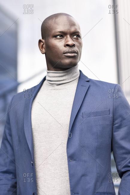 Portrait of businessman wearing blue suit and grey turtleneck pullover