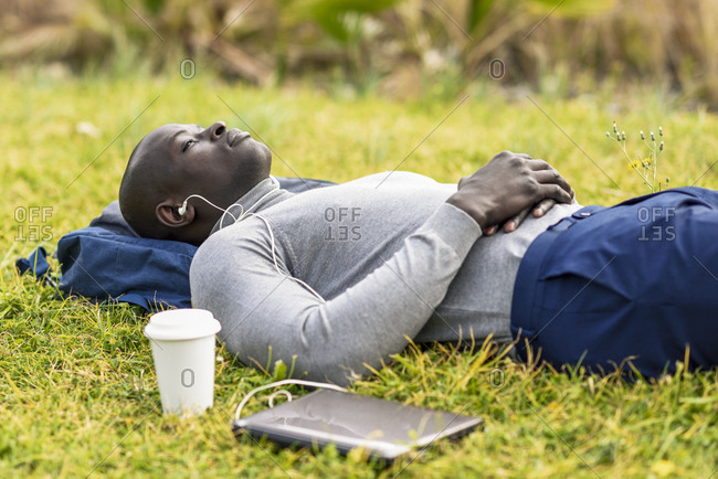 Businessman lying on a meadow listening music with earphones and laptop