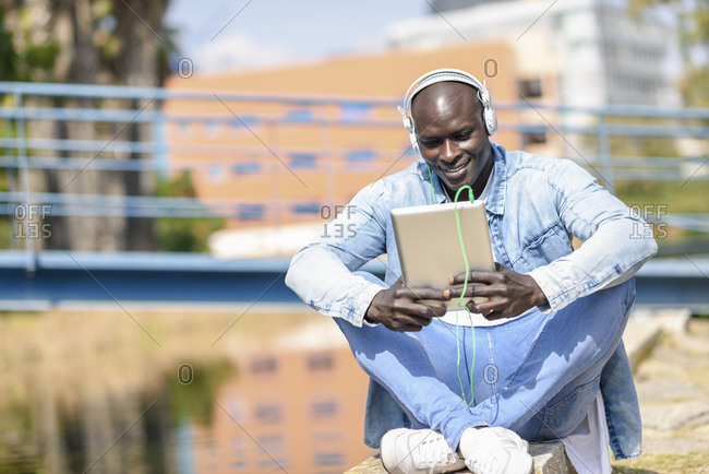 Man wearing casual denim clothes  listening music with headphones and digital tablet outdoors