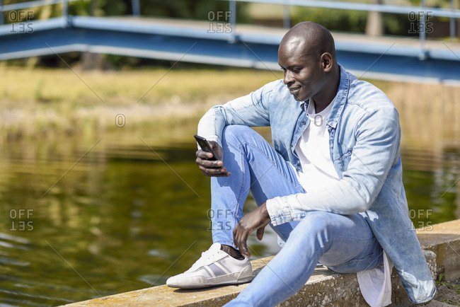 Man wearing casual denim clothes sitting near river using smartphone