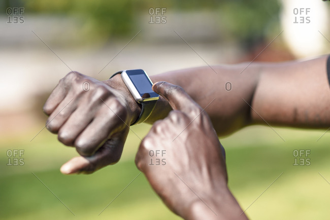 Runner checking smart watch fitness tracker- close-up