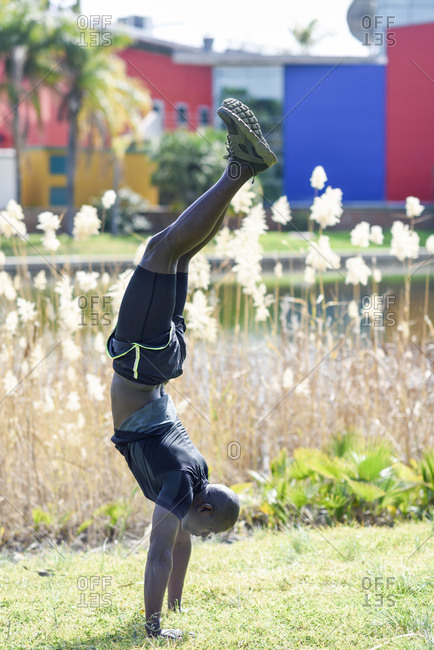 Man in black sportswear doing handstand on a meadow