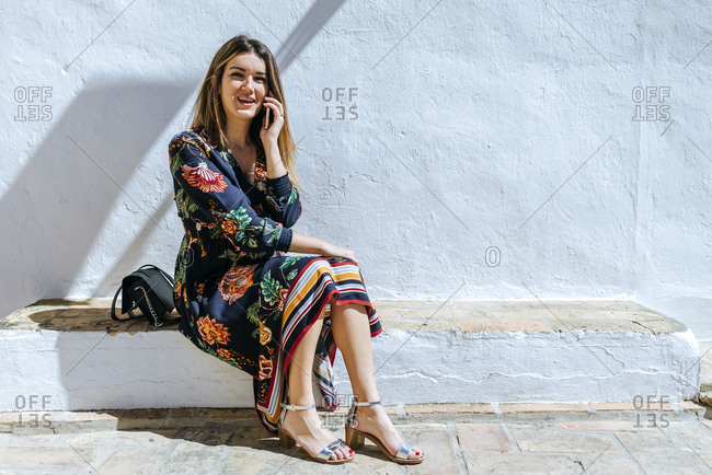 Spain- Cadiz- Vejer de la Frontera- portrait of fashionable woman on the phone sitting on wall