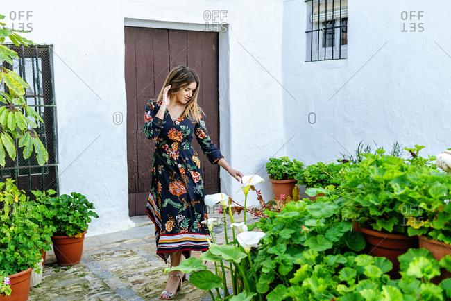 Spain- Cadiz- Vejer de la Frontera- fashionable woman looking at Callas at patio