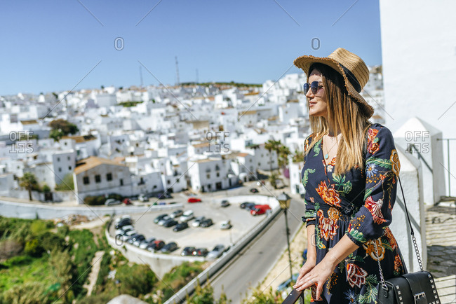 Spain- Cadiz- Vejer de la Frontera- fashionable woman standing on roof terrace looking at view