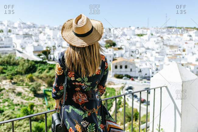 Spain- Cadiz- Vejer de la Frontera- back view of fashionable woman on roof terrace looking at view