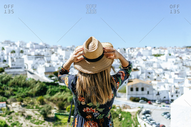 Spain- Cadiz- Vejer de la Frontera- back view of woman wearing straw hat looking at view