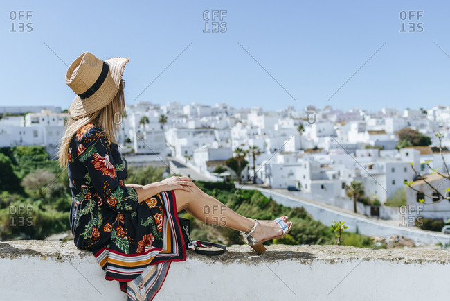 Spain- Cadiz- Vejer de la Frontera- fashionable woman sitting on balustrade looking at view