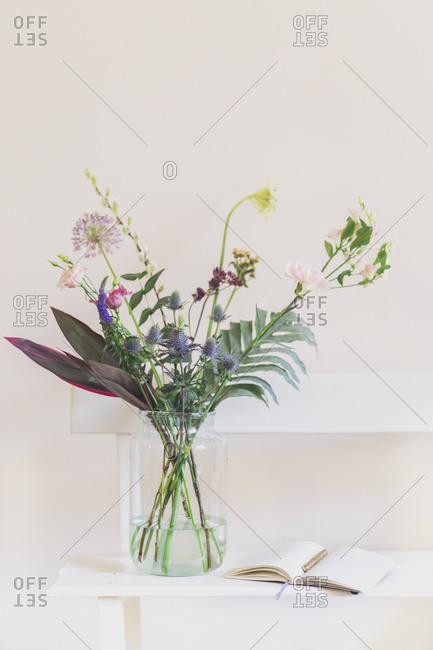 Flower vase and open calendar on white bench