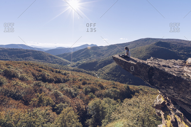 Spain- Navarra- Irati Forest- woman sitting on rock spur above forest landscape in backlight