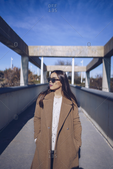 Young woman wearing coat and sunglasses standing on a bridge