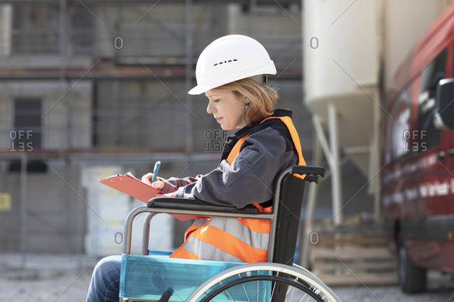 Woman wearing reflective vest and hard hat sitting in wheelchair taking notes